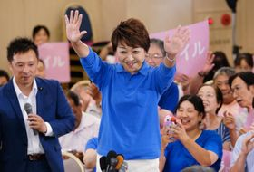 当選確実の報を受け、手を振って喜ぶ永江孝子さん(中央)=21日午後8時10分ごろ、松山市大手町1丁目
