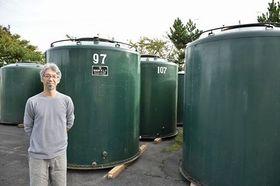 板柳町の旧店舗から運び込んだ貯蔵タンクを背に決意を語る令晃さん