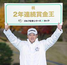 2年連続の賞金王となり、ボードを掲げる今平周吾=東京よみうりCC
