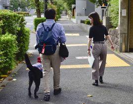 採用試験を終え、職員(右)の誘導で会場を出た受験者=15日午後、東京都千代田区