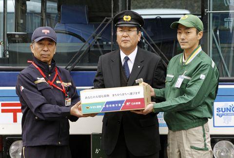路線バスの前で写真に納まる(左から)日本郵便、宮崎交通、ヤマト運輸のドライバー=20日、宮崎県西米良村