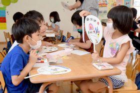熊本県の豪雨被災者に届けるうちわを作る子どもたち=丸亀市郡家町、誠心こども園