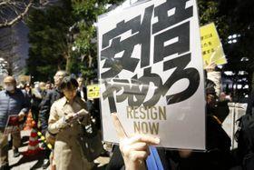 「安倍やめろ」と書かれたプラカードを手にする参加者=13日午後7時50分ごろ、東京・千代田区の首相官邸前