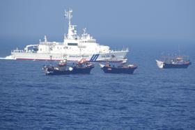 2019年6月、日本海の大和堆周辺で北朝鮮漁船(手前)に退去警告をする海上保安庁の巡視船(同庁提供)