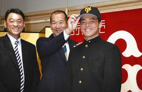 巨人と仮契約を結び、長谷川国利スカウト部長(左)と担当の織田淳哉主任(中)から巨人の帽子をかぶせてもらう星稜高・山瀬慎之助捕手=金沢市内のホテルで