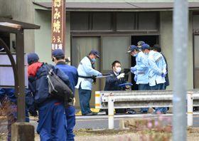 血を流した高齢女性が見つかった現場付近を調べる捜査員ら=18日午前11時22分、広島市安佐北区