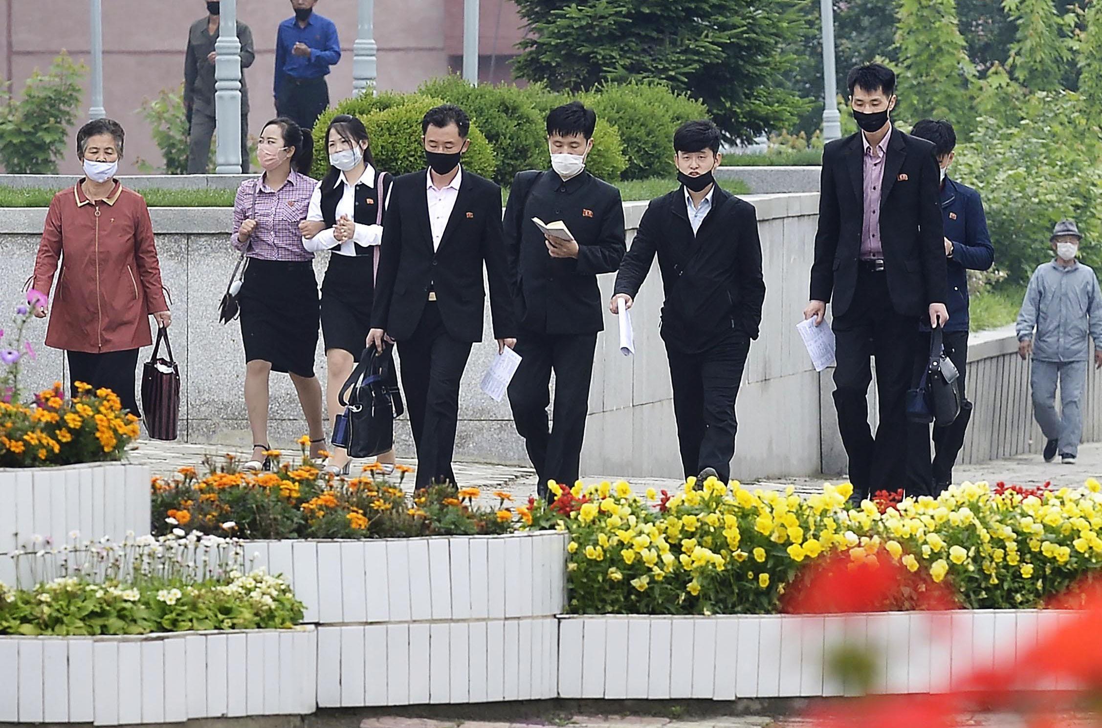 マスク姿で平壌市内を歩く人たち=27日(共同)