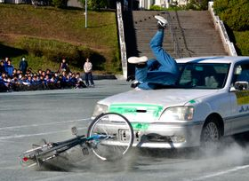 【スタントマンによる交通事故実演=亀山市田村町の市立中部中学校で】