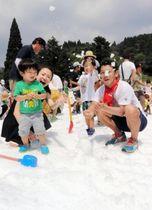 冷たい雪の感触に喜ぶ親子=六甲山カンツリーハウス