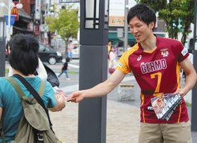 開幕戦に向け駅前でチラシを配る選手ら=松本市の松本駅前で