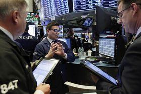 ニューヨーク証券取引所のトレーダーたち=22日(AP=共同)