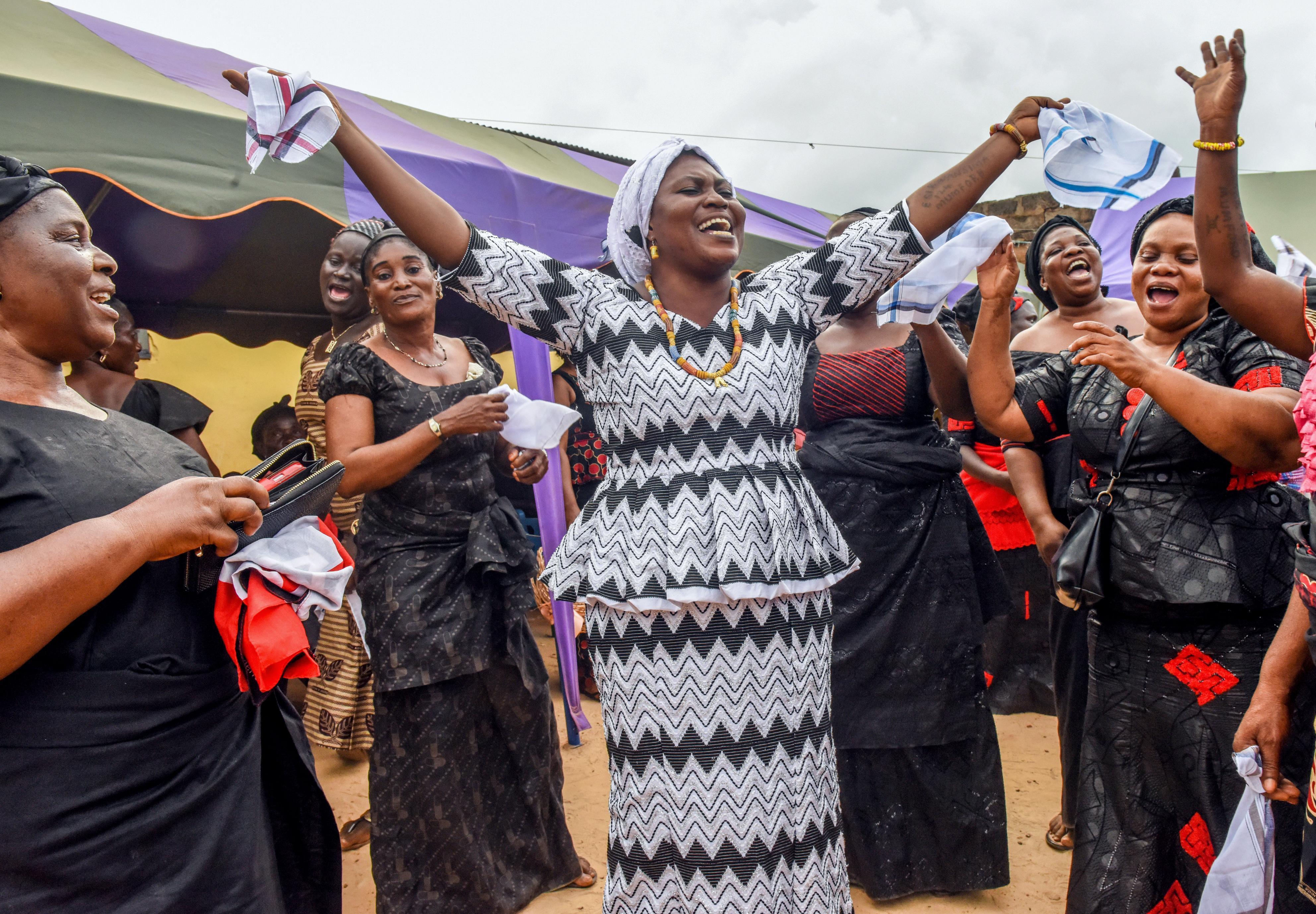 ジョセフの埋葬を終え、音楽に合わせ踊る娘のアイビー(中央)。参列者の笑顔が彼女を元気にした=ガーナ南部マンフォード(撮影・中野智明、共同)