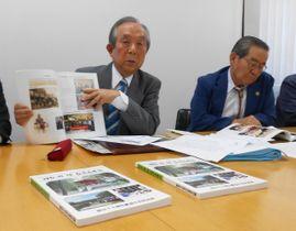 完成した記念誌を説明する石川さん(左)