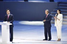 平昌冬季五輪の開会式から1年を記念した行事で演説する韓国の李洛淵首相(左)と拍手するフィギュアスケートの元五輪女王の金妍児さん(右)=9日、韓国・江陵(共同)