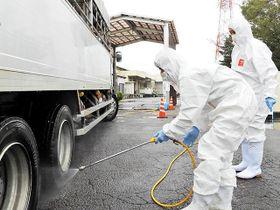 関市食肉センターが再開し、入り口で搬入トラックを消毒する職員たち=21日午前9時17分、関市西田原