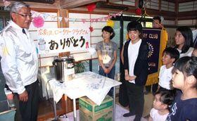 寄贈したスープ保温器具を前に子どもたちにあいさつをする粟屋会長(左端)