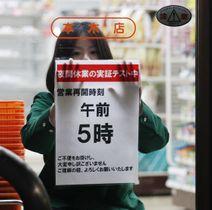 セブン―イレブンが3月に行った時短実験で、深夜休業後の営業再開時刻について、お知らせを張る店員=東京都内