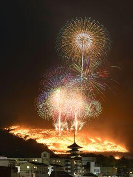 古都奈良の夜空に浮かび上がった「若草山焼き」。手前は興福寺の五重塔=25日(午後6時19分から午後7時28分まで多重露光)