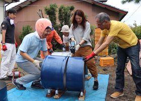 モモの被り物をした紀の川市職員と協力しながらドラム缶を切断する参加者=雲仙市千々石町