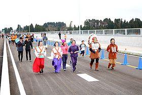 開通したバイパスをウオーキングやランニングを楽しむ人たち=砺波市頼成