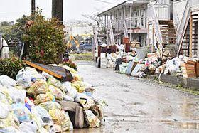 住宅やアパートの前に積み上げられた災害ごみ。雨で住民の姿は少なく、河川復旧工事の音が響いていた=22日午前、本宮市