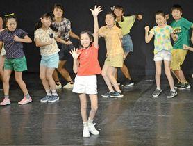歌や踊りを通して地球環境の保護を訴える、あいちゃん役の足立琴春さん(手前)ら子どもたち=松江市美保関町七類、メテオプラザ
