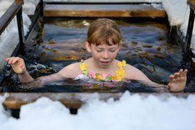 氷点下16度の気温の中で、凍結した氷をくり抜き、川に漬かる少女=19日、ロシア極東サハリン州(タス=共同)