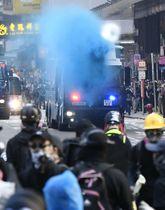 デモ隊の若者ら(手前)に向けて青色の水を噴射する放水車=20日、香港・九竜地区(共同)