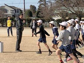 「腕を使って、つま先で歩いて」と走りの基礎から児童に教える高野進さん=伊奈町立南小学校