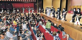 総おどり「金沢風雅」で芸妓がまく手ぬぐいに手を伸ばす観客=金沢市の石川県立音楽堂邦楽ホール