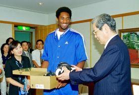 笹山幸俊市長にサイン入りのバスケットボールシューズをプレゼントするコービー・ブライアント選手=1998年8月26日、神戸市役所