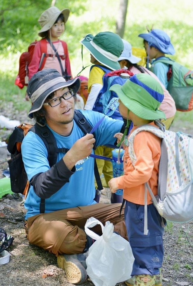 入ったばかりの子どもの手助けをする野沢俊索。子どもたちはやがて、お弁当の準備や片付けなど、自分のことは自分でするようになる=兵庫県西宮市の甲山森林公園