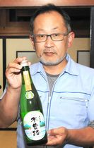 トンネル内で熟成させた純米吟醸酒を手にする湯川さん