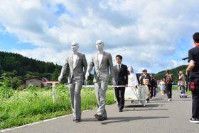 厳しい暑さの中、「花嫁行列」の場面を撮影する関係者たち=25日、八戸市南郷島守
