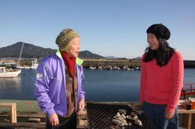 宮島(奥左)を望む玖波漁港で、カキ祭りについて話し合う沖田さん(右)と三紙代表