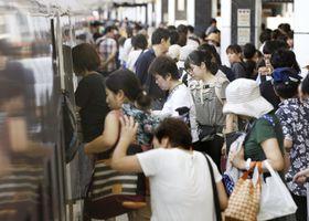 お盆を古里や行楽地で過ごす人たちで混雑するJR東京駅の新幹線ホーム=11日午前