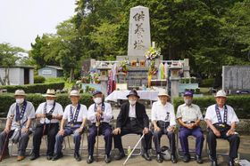 供養塔前で写真に納まる「八七会」の会員=7日午後、愛知県豊川市