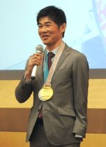 平昌冬季パラリンピックで獲得した金銀メダルを胸に、あいさつする新田佳浩選手=23日、東京都品川区