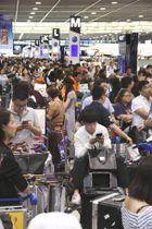 システム障害の影響で、搭乗手続きを待つ乗客らで混雑する成田空港第2ターミナル=18日午後