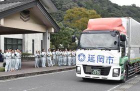 支援物資のペットボトル5000本を載せて福島県いわき市に向けて出発するトラック=17日午後・延岡市北川町