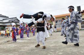 「見せ場」で女性を抱え上げて踊る、元禄坊主踊り保存会メンバー