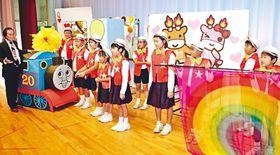学習発表会に向け気持ちを高める児童。見守る山本さん(左)