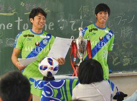 ルヴァン・カップのトロフィーを前に児童らと話す梅崎選手(左)と新井選手=平塚市で