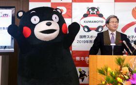 4日、海外企業によるくまモン(左)のイラスト利用解禁を発表した熊本県の蒲島郁夫知事=熊本県庁