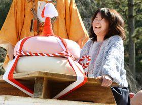 京都・醍醐寺の「餅上げ力奉納」で、特大鏡餅の持ち上げに挑戦する女性参加者=23日午後