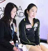 スケートカナダ女子SPの演技を終え、得点を待つ間に舌を出す本田真凜。左は浜田美栄コーチ=レジャイナ(共同)