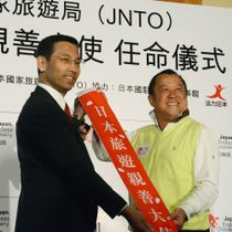 2011年に「日本旅行親善大使」に任命され、たすきを渡される俳優エリック・ツァンさん(右)=2011年11月27日