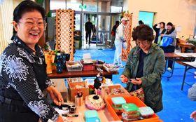 「おいしいからまず食べて」。手作りの漬物を勧める比嘉信子さん(左)