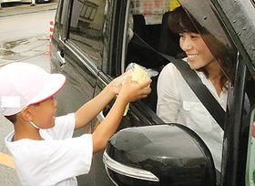 ドライバーにナシを手渡す園児(左)