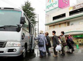 三次市内の商業施設で買い物を終え、マイクロバスに乗り込むツアー参加者たち